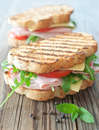 Grilled deli sandwiches with ham and cheese on top of a chopping board  Stock Photo