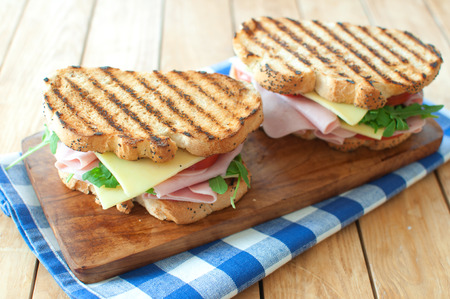 ham sandwich: Grilled sandwiches with ham and cheese on top of a chopping board