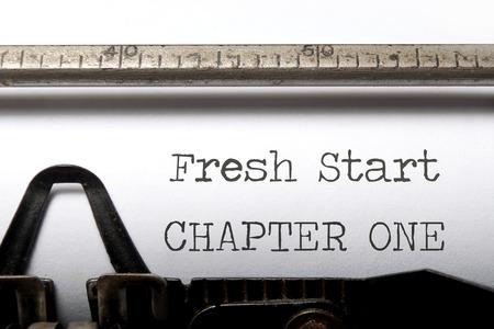 frisse start: Nieuw hoofdstuk één start afgedrukt op een oude typemachine Stockfoto