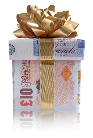 christmas profits: Gift box wrapped with sterling pound banknotes with a gold silk ribbon Stock Photo