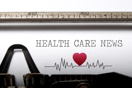 Health care news printed on an old typewriter with heart beat pulse sketch Foto de archivo