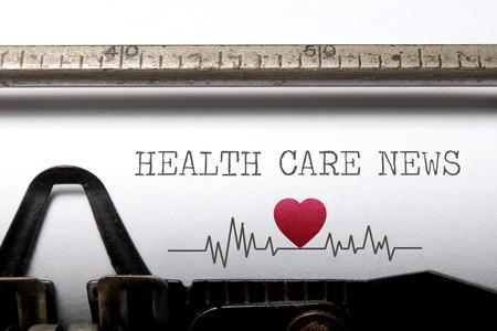 Les soins de santé nouvelles imprimé sur une vieille machine à écrire avec battement de coeur impulsion croquis Banque d'images