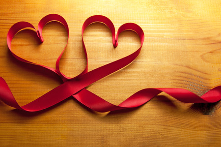 Red ribbons made from silk in the shape of hearts photo