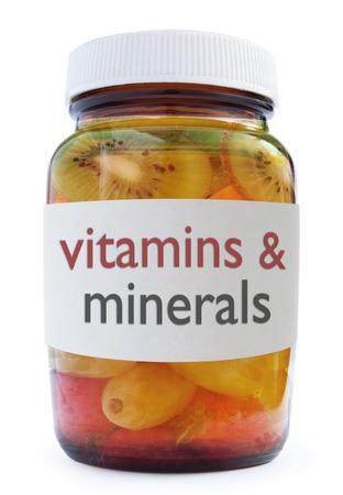 over packed: Bottiglia Vitamine e minerali medicina pieno di frutta su uno sfondo bianco
