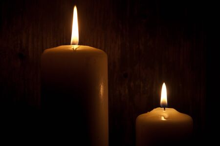 black worship: Two lit candles in the dark Stock Photo