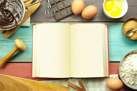 Open blank recipe book surrounded with ingredients Stock Photo