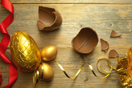 chocolate eggs: Gold easter egg with broken chocolate pieces