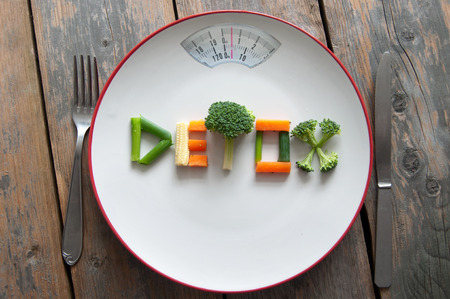 spring onions: Detox text on a plate made from various vegatables including broccoli, spring onions and carrots