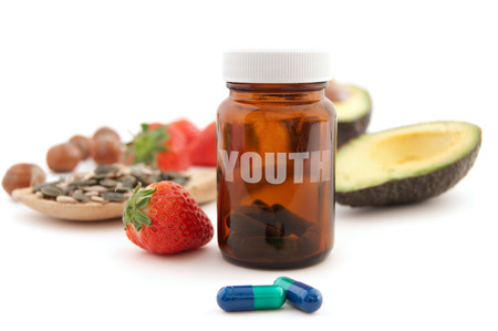antiaging: Anti-aging pills surrounded by nutritious superfoods including avocado, pumpkin seeds and berries
