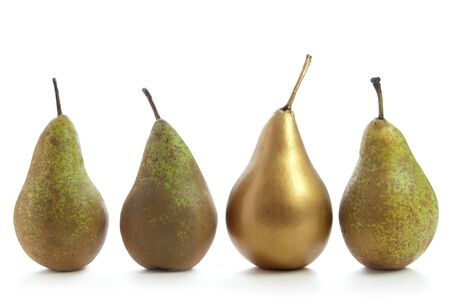 superiors: Unique gold pear standing out in a row of fruit over a white background Stock Photo