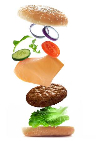 comida chatarra: Volar ingredientes de la hamburguesa Foto de archivo