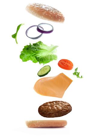 bollos: Ingredientes de la hamburguesa que caen en su lugar para crear un emparedado en un fondo blanco Foto de archivo