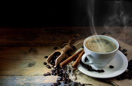 Hot coffee in a cup with beans on a wooden background with space Stock Photo