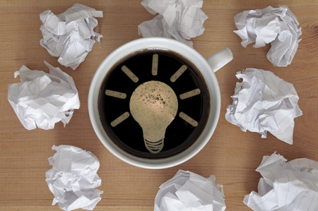 writers block: Light bulb symbol inside a coffee cup symbolizing new idea Stock Photo