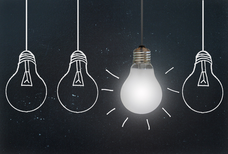 Bright hanging light against a row of drawn bulbs on a blackboard Stockfoto