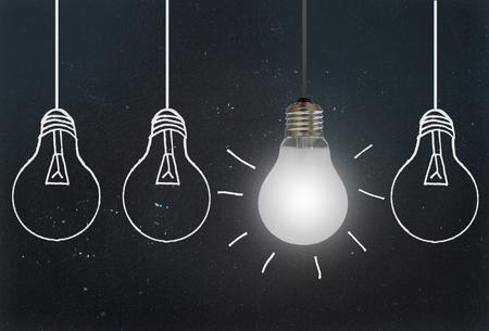 Hanging luz brillante contra una fila de bombillas dibujado en una pizarra Foto de archivo - 45289904