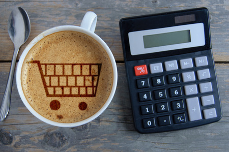 grocery shopping cart: Shopping cart symbol inside a coffee cup by a calculator Stock Photo