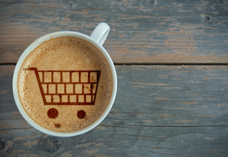 shop online: Shopping cart symbol inside a cup of coffee with space