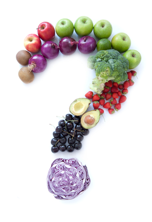 Question mark made from fruits and vegetables over a white background