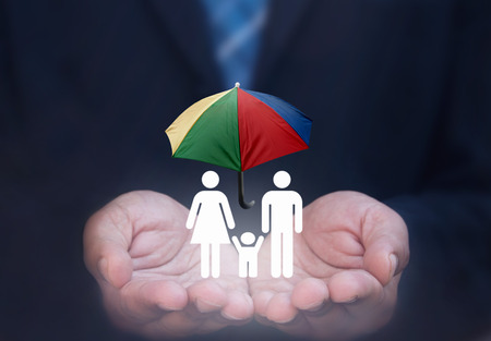 household accident: Business man holding lit up house symbol with umbrella protection