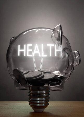 cost: Piggybank light bulb with health lit text inside Stock Photo