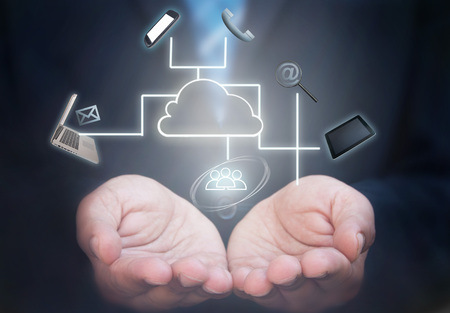 Business man holding a network of computer gadgets and social media icons stemming from a cloud icon Stockfoto