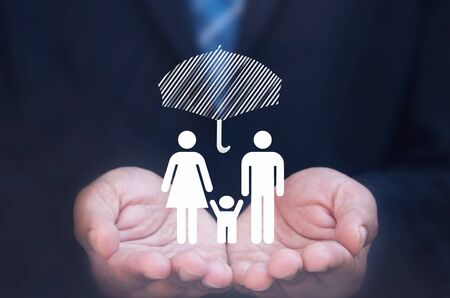 household accident: Business man holding a family icon protected by an umbrella Stock Photo