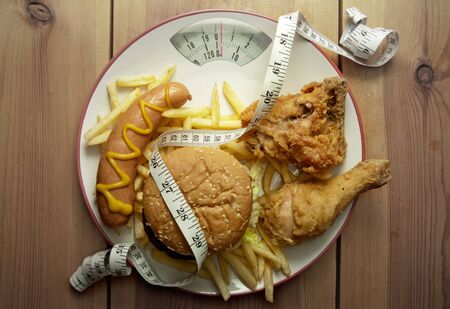 junk: Plate packed with junk food with weighing scales Stock Photo