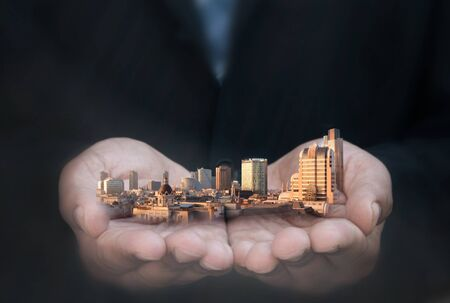 financial insurance: Business man holding city skyline skyscrapers and buildings
