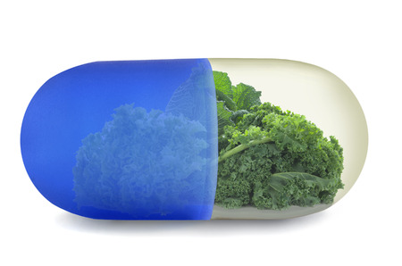 vitamin pill: Close up of a vitamin pill with green vegetables including kale, cabbage and lettuce