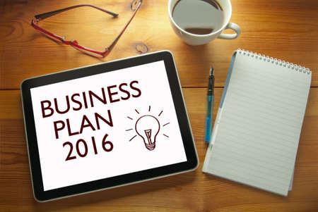 investment ideas: Work desk with computer tablet document entitled business plan 2016 Stock Photo