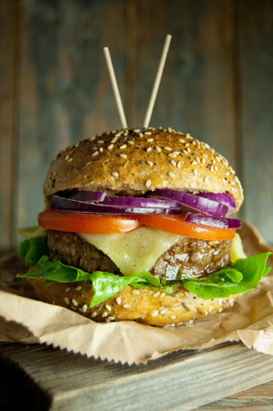 grilled vegetables: Gourmet burger with melted cheese, tomato and onion filling on top of a wooden chopping board