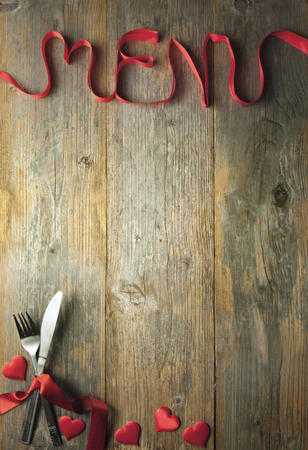 menus: Valentine menu background made from red ribbon bow with cutlery and baubles