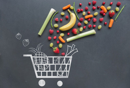 Grocery shopping cart sketched on a chalkboard combined with fruits and vegetables