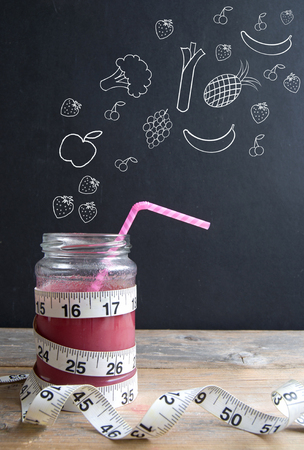 cinta metrica: Berry batido con cinta métrica y frutas y verduras que aparecen 'verter' esbozado en una pizarra