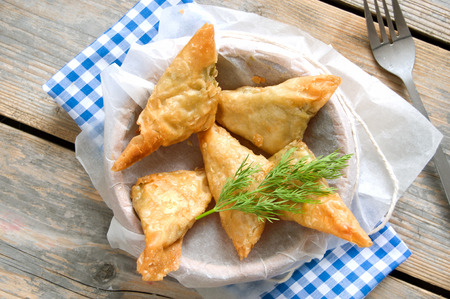 filo pastry: Greek cheese stuffed filo pastry with herbs in a dish on a wooden background