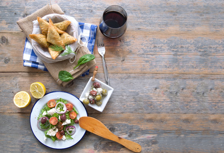 Feta cheese and spinach filo pastries and greek salad laid out on a wooden table