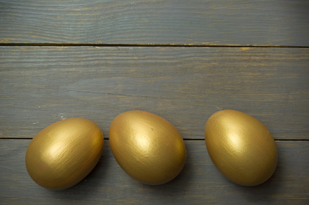 gold eggs: Gold eggs over a wooden background