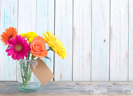 Mixed variety of flowers in a glass jar over a white background