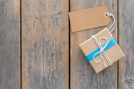 tied in: Gift box tied in blue ribbon over a wooden background