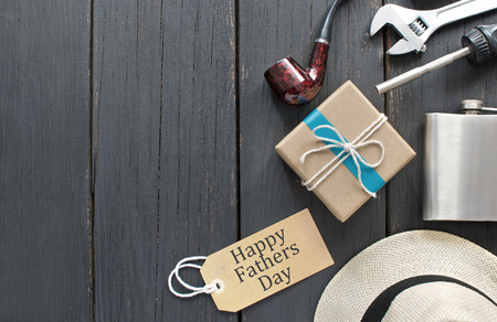 Fathers day gift box tied in blue ribbon over a wooden background with label