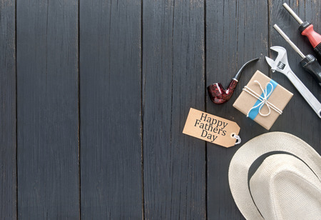 tied in: Fathers day gift box tied in blue ribbon over a wooden background with label