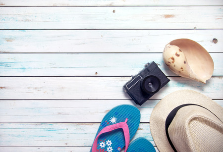 Vacation items, inluding sunglasses, and camera, on white wooden planks with space