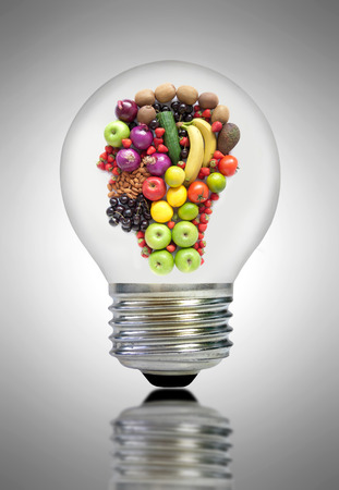 head shape: Fruit and vegetable ingredients inside a light bulb in the shape of a human head Stock Photo