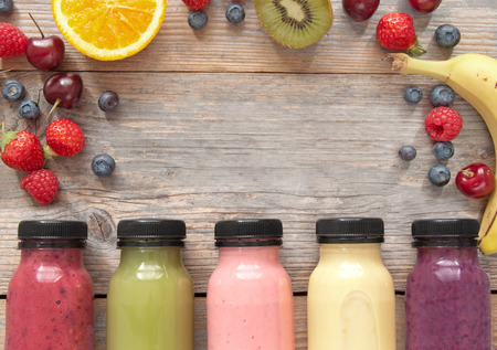 fruit background: Assorted flavoured smoothie juices in bottles over a wooden background with fruit Stock Photo
