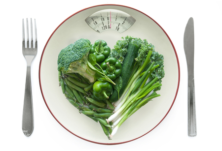 weighing scales: Heart shape vegetables on a plate with diet weighing scales monitor Stock Photo