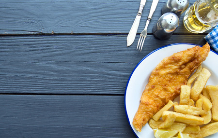 haddock: Deep fried fish and chips on a wooden table with space Stock Photo