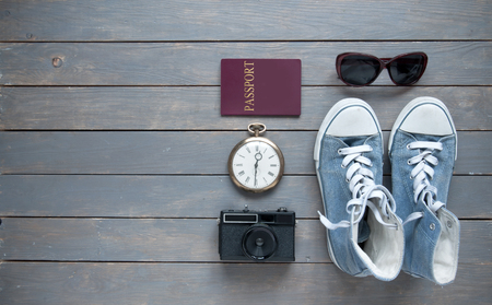 Travel items on a wooden background with passport, camera and shoes