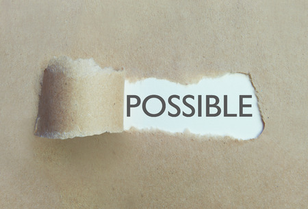 uncovering: Torn brown paper uncovering the word possible