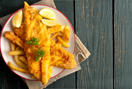 Close up of battered fish on a plate with chips Imagens